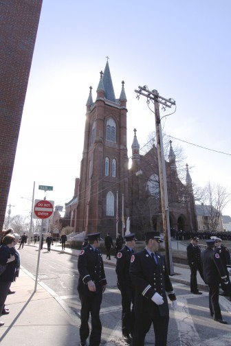 Firefighters stand in the shadow of St. Patrick's Church after Lt. Edward Walsh's wake. Photo by Charlie Breitrose