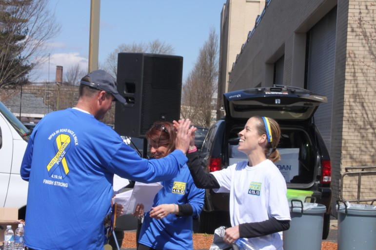 Top female runner Jill Wilder of Waltham gets a high five from Watertown Police Lt. Michael Lawn, the Finish Strong Road Race organizer.