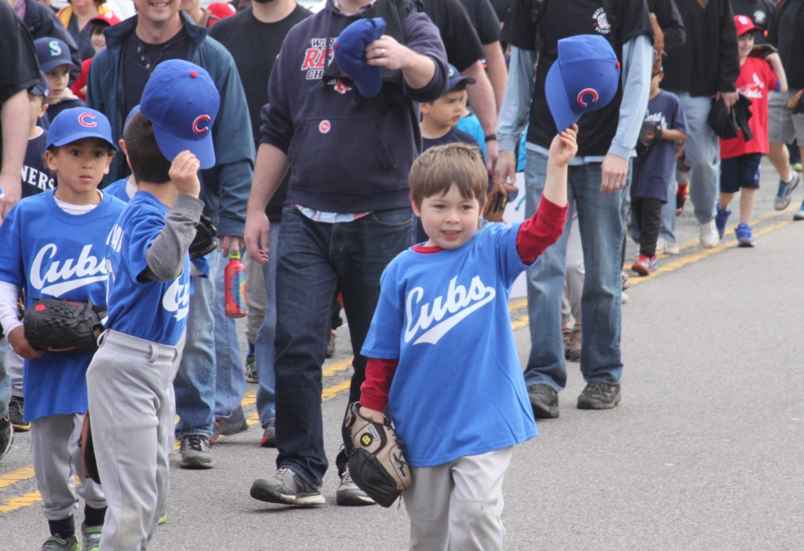 Young Watertown Baseball players march toward Casey Field for opening day.