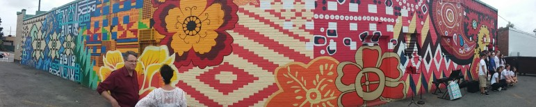 A panorama photo of the Tapestry of Cultures mural on Baptist Walk in Watertown Square.