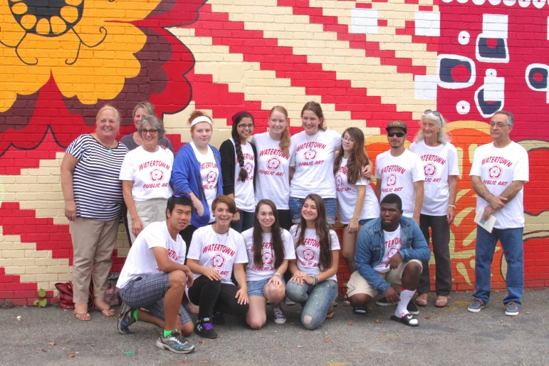 """Students who painted the """"Tapestry of Cultures"""" mural in Watertown Square pose with members of the Watertown Cultural Council."""