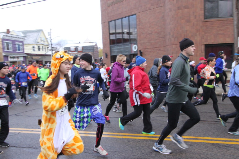 Runners take off at the start of the Donohue's Turkey Trot, including a woman dressed as a giraffe.