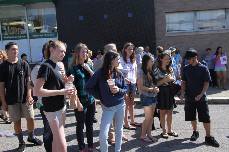 Watertown High School students chat with artist and mentor Gregg Bernstein during the celebration of the new mural they painted in Coolidge Square