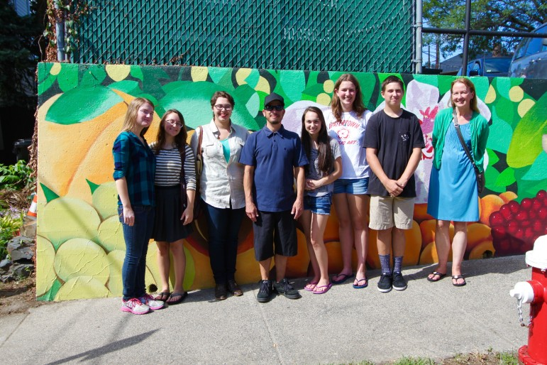"""Some of the student artists who painted the mural """"Seeds of Change"""" in East Watertown, with artist Gregg Bernstein, center, and Watertown High School art teacher Donna Calleja."""