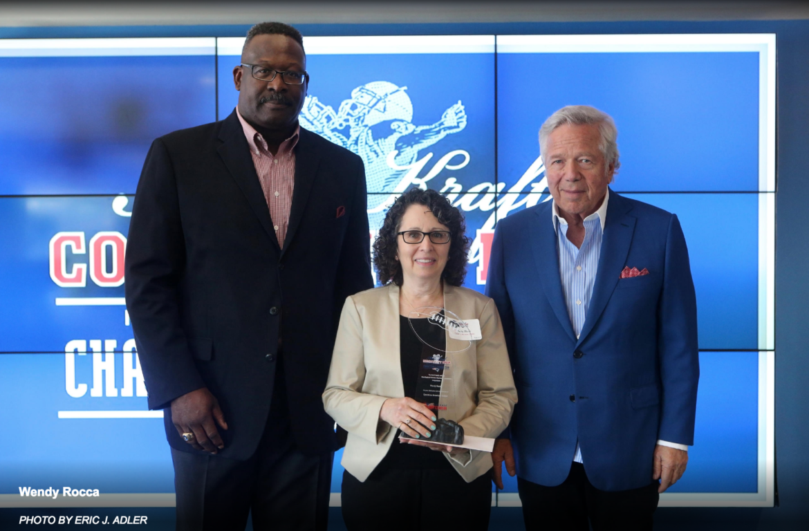 Wendy Rocca, co-founder of Operation American Soldier, received the Myra Kraft Community MVP Award from New England Patriots owner Bob Kraft, right, and Patriots Executive Director of Community Affairs Andre Tippett, left.